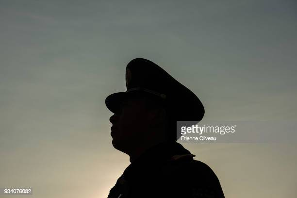 Paramilitary policeman stands guard on Tiananmen Square before the seventh plenary session of the 13th National People's Congress at the Great Hall...