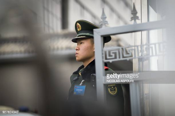 A paramilitary policeman stands guard outside a hotel where Guangdong delegation holds a meeting during the National People's Congress China's...