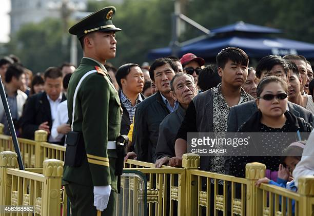 A paramilitary policeman watches over visitors lining up for a security check at the entrance to Tiananmen Square in Beijing on the eve of National...