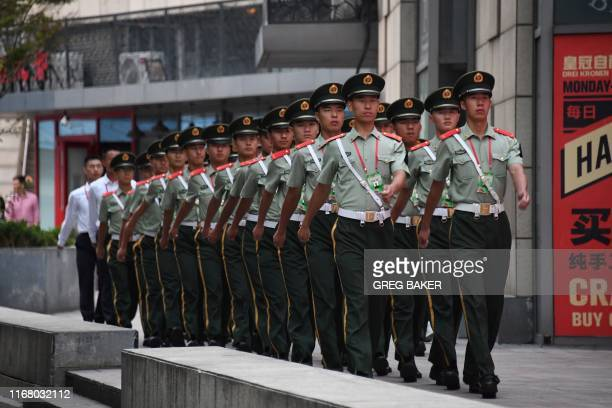 Paramilitary policemen march behind a mall next to the Worker's Stadium ahead of an overnight rehearsal of a military parade in Beijing on September...