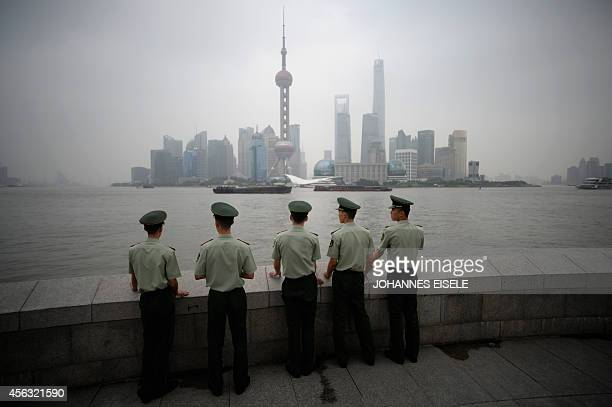 Paramilitary policemen stand in front of the skyline of the Lujiazui Financial District in Pudong in smog in Shanghai on September 29 2014 China...
