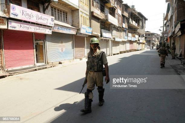 Paramilitary soldier stands guard in a closed market during a strike at Maisuma on June 25 2018 in Srinagar India Joint Resistance Leadership of Syed...
