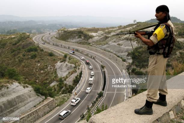A paramilitary soldier stands guard overlooking a highway as the first batch of Hindu pilgrims leave for Amarnath Yatra an annual pilgrimage to the...