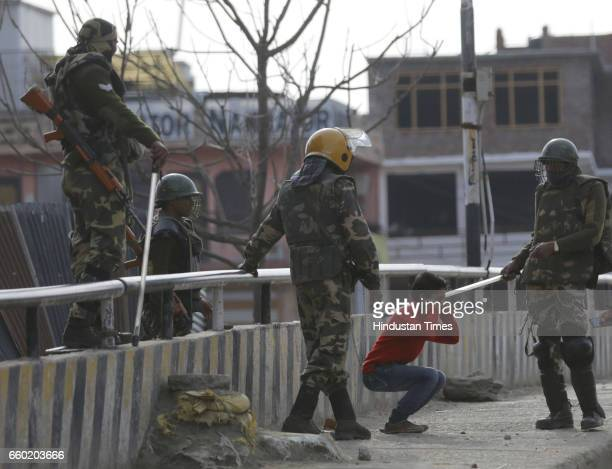 Paramilitary soldiers force a child to perform situps while holding his ear before letting him go during a strike against the killing of civilians on...