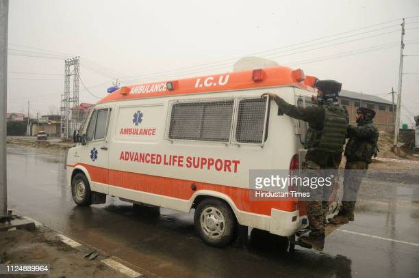 Paramilitary soldiers hang on to an ambulance carrying bodies of their colleagues near the site of an explosion on the JammuSrinagar highway on...