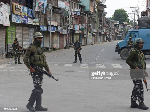 Paramilitary soldiers stand guard during curfew on Eid alAdha at Lal Chowk on August 12 2019 in Srinagar India The festive buzz was missing in...