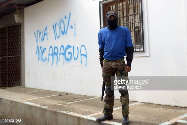TOPSHOT A paramilitary stands guard in a street of Monimbo neighborhood next to a grafitti reading Long live Nicaragua 100% in Masaya Nicaragua on...