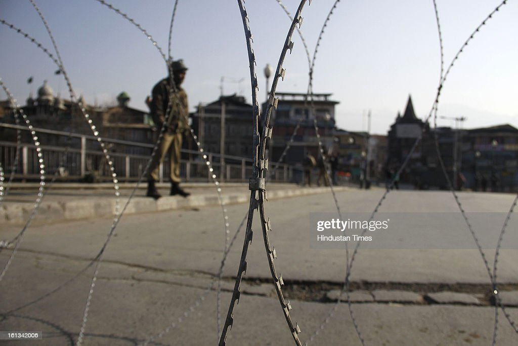 Paramilitary troop stands guard behind barbed wire on deserted street after the parliament attack convict, Muhammad Afzal Guru was hanged in New Delhi, during Second day curfew on February 10, 2013 in Srinagar, India. Guru, who was found guilty of conspiring and sheltering the militants who attacked Parliament on December 13, 2001 in which nine people were killed, was buried in the prison premises as per the jail manual.