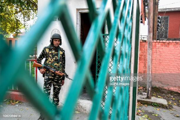A paramilitary trooper keeps vigil outside the polling station during the third phase of local elections in Srinagar Indian administered Kashmir The...