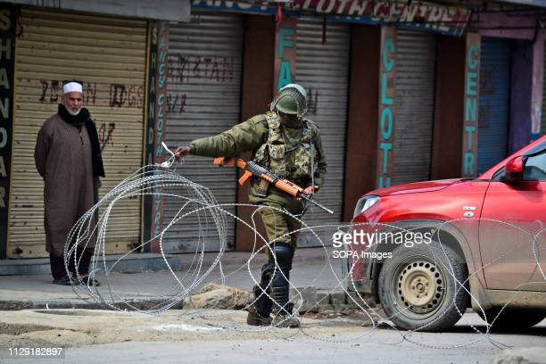 A paramilitary trooper seen removing barbed wire to let a vehicle pass during restrictions in Srinagar Kashmir Authorities imposed restrictions in...