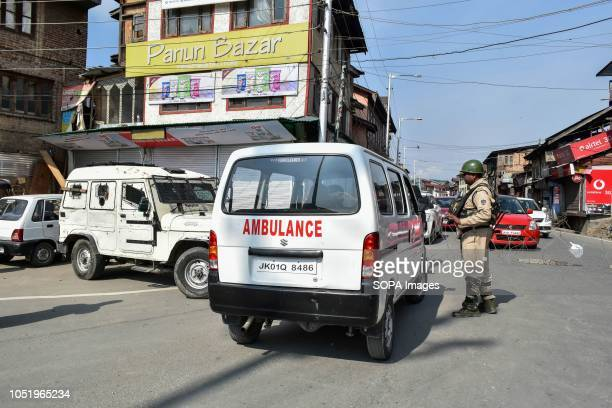 A paramilitary trooper stops an ambulance during restrictions in Srinagar Indian administered Kashmir Authorities impose restrictions in Srinagar...