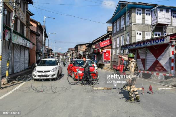 A paramilitary trooper stops vehicles during restrictions in Srinagar Indian administered Kashmir Authorities impose restrictions in Srinagar amid a...