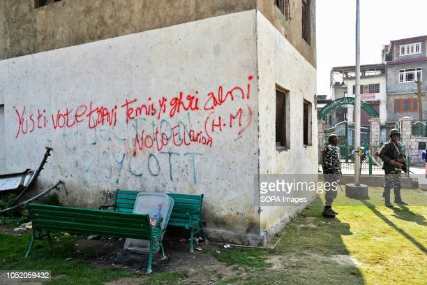 Paramilitary troopers stand guard next to a wall with antielection graffiti inside the polling station during the third phase of local elections in...