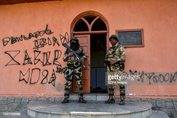 Paramilitary troopers stand guard outside the polling station during the third phase of local elections in Srinagar Indian administered Kashmir The...