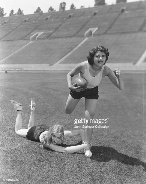 Paramount actresses Virginia Bruce and Lillian Roth play football at a football stadium Bruce and Roth both starred in films primarily from the 1930s...