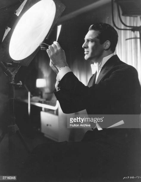 Paramount film player Cary Grant examines test footage from his previous day's work in B P Schulberg's film 'Kiss And Make Up'.