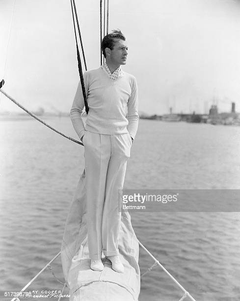 Paramount Pictures publicity portrait of Gary Cooper. He is shown full-length, standing on the prow of a sailboat. Photograph, circa 1939.