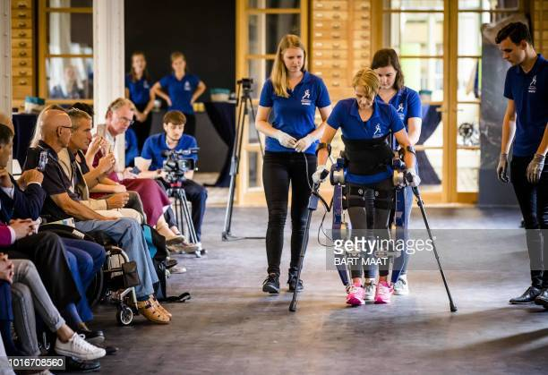 Paraplegia patient Sjaan Quirijns uses crutches to support her steps in an exoskeleton during a presentation at the Technical University Delft in...