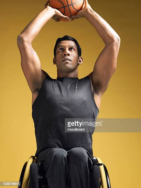 paraplegic athlete, sitting in wheelchair shooting basketball - paraplegic stock photos and pictures