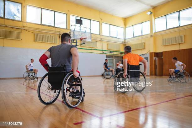 paraplegic basketball athletes playing a match in a indoors sports court - adaptive athlete stock pictures, royalty-free photos & images