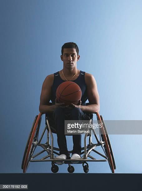 Paraplegic male athlete holding basketball, portrait