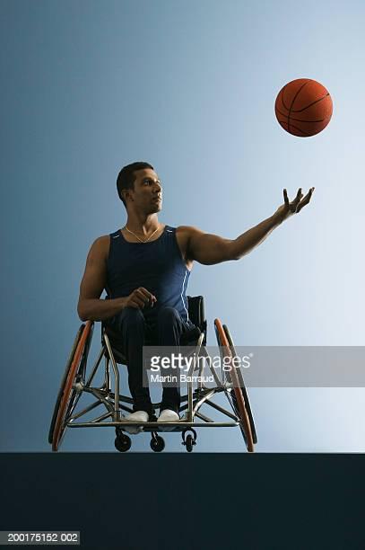 Paraplegic male athlete throwing basketball in air