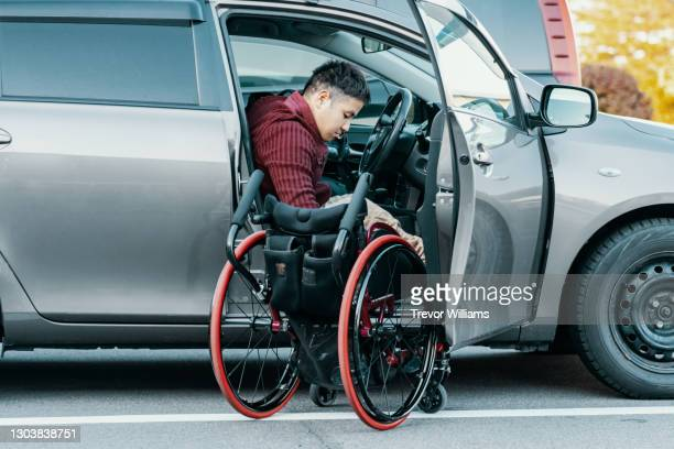 paraplegic man in a wheelchair getting in or out of his car - physical disability stock pictures, royalty-free photos & images