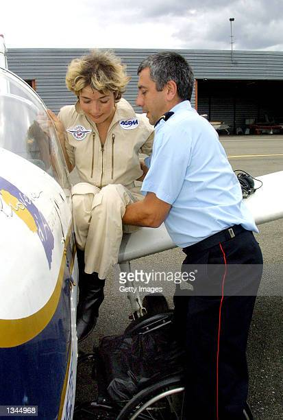 Paraplegic pilot for the fire and rescue department, Dorine Bourneton, is helped into the cockpit of her plane August 19, 2002 in Cahors, France....