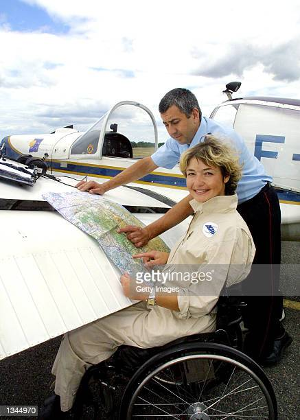 Paraplegic pilot for the fire and rescue department, Dorine Bourneton, reviews a map next to the cockpit of her plane August 19, 2002 in Cahors,...
