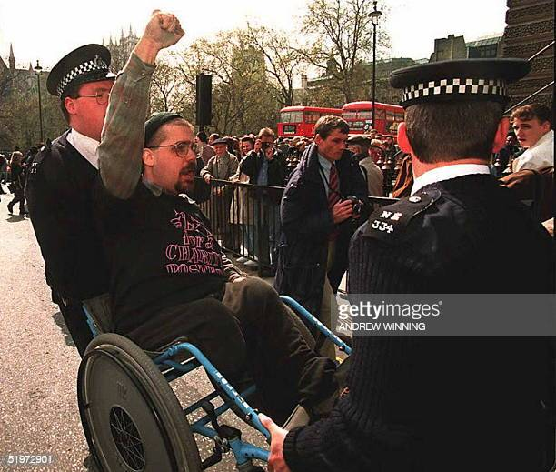 Paraplegic protester is carried from the road in his wheelchair by police officers during a protest in favor of a bill which would help disabled...