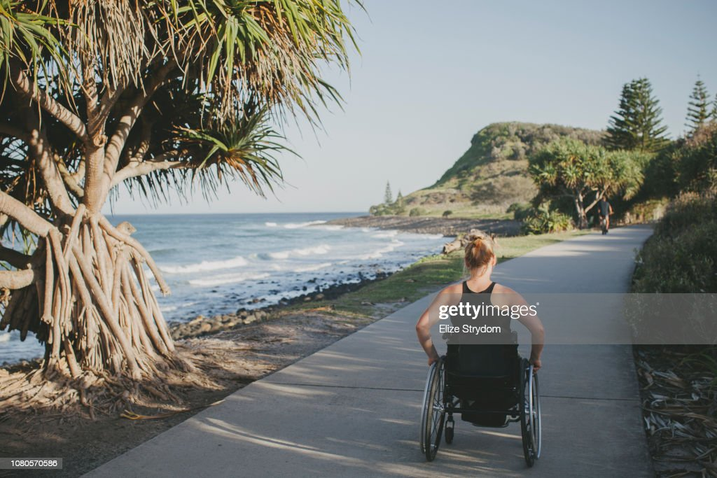 Paraplegic woman by the ocean : Stock Photo