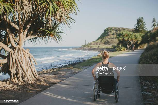 paraplegic woman by the ocean - paraplegic stock photos and pictures