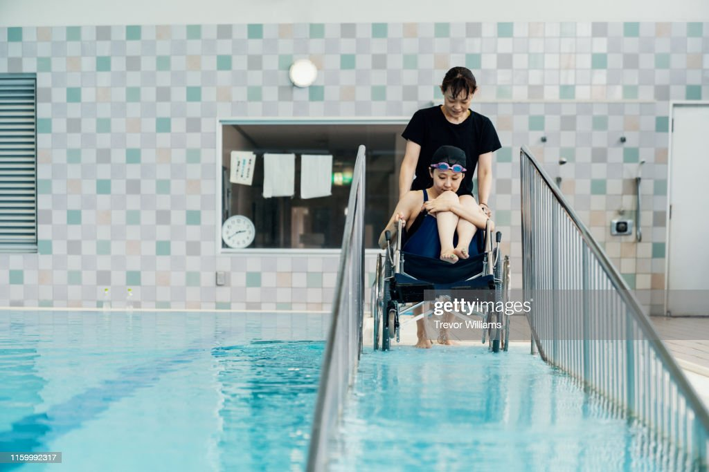 Paraplegic woman in a wheelchair and her coach entering or leaving the pool before or after training for competitive swimming : ストックフォト