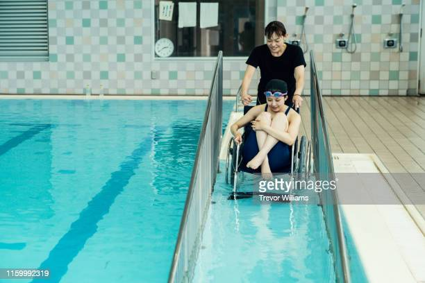 Paraplegic woman in a wheelchair and her coach entering or leaving the pool before or after training for competitive swimming