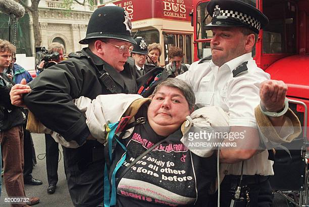 Paraplegic woman is carried from in front of a bus by two policemen on London's Whitehall 18 May 1994 after a group of disabled people stopped the...