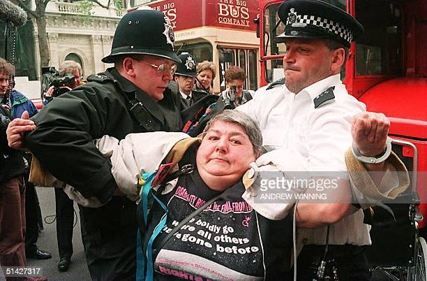 Paraplegic woman is removed from in front of a bus by two policemen on London's Whitehall 18 May 1994 after a group of disabled people stopped...