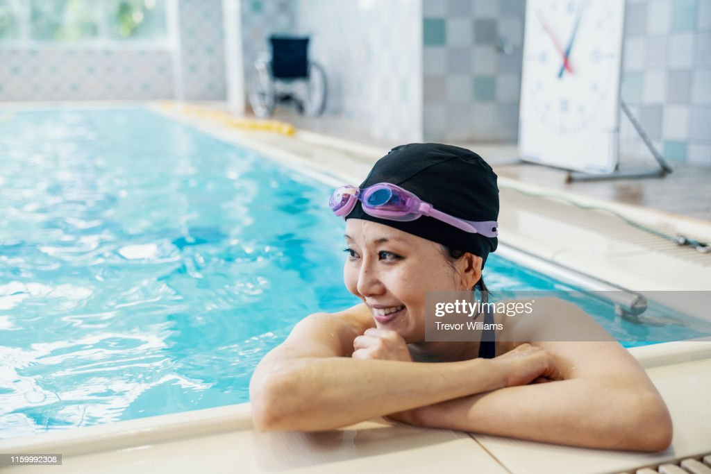 Paraplegic woman is resting inside a pool while training for competitive swimming : ストックフォト