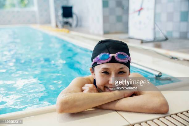 paraplegic woman is resting inside a pool while training for competitive swimming - スポーツ施設 ストックフォトと画像