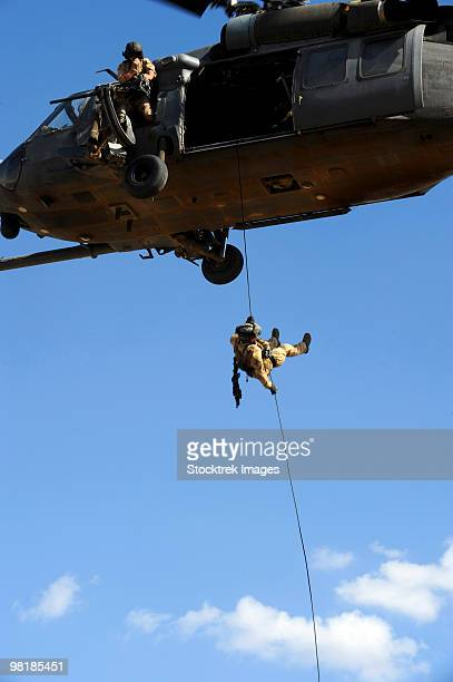 A pararescueman rappels from an HH-60 Pavehawk helicopter.