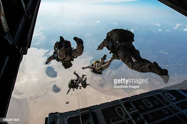U.S. Pararescuemen and U.S. Marines jump from a HC-130 over Djibouti.