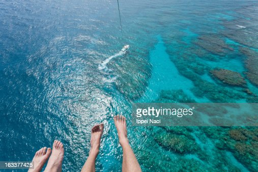 Parasailing over coral reef and tropical water
