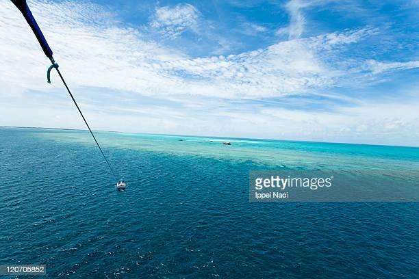 Parasailing over coral reef, Okinawa, Japan