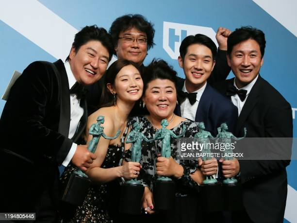 TOPSHOT Parasite cast Song Kangho Cho Yeojeong director Bong Joonho Lee Jungeun Choi Wooshik and Lee Sunkyun pose with the trophy for Outstanding...