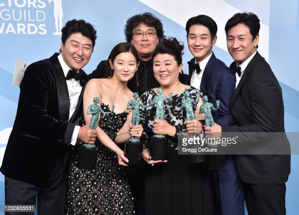 Parasite cast Song Kangho Cho Yeojeong director Bong Joonho Lee Jungeun Choi Wooshik and Lee Sunkyun pose in the press room with the trophy for...