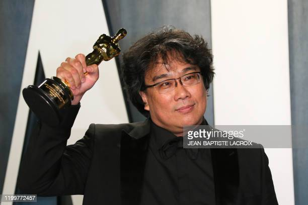 """Parasite"" director Bong Joon-ho poses with the Oscar for Best Screenplay for ""Parasite"" as he attends the 2020 Vanity Fair Oscar Party following the..."