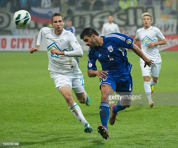 Paraskevas Christou of Cyprus heads the ball in front of Tim Matavz of Slovenia during the World Cup 2014 qualifier football match Slovenia vs Cyprus...