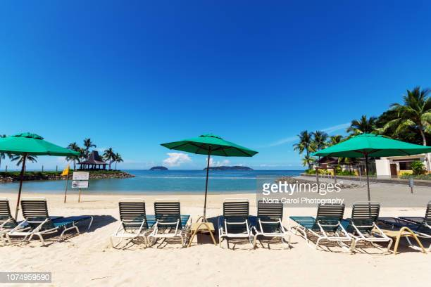 parasol and beach deck chair at kota kinabalu beach - sabah state stock pictures, royalty-free photos & images