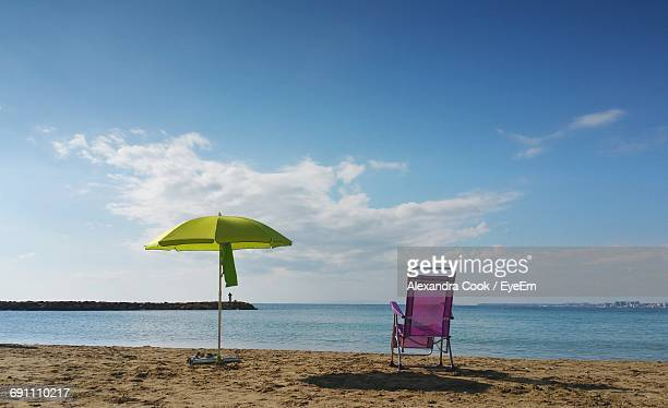 Parasol And Deck Chair On Beach Against Sky