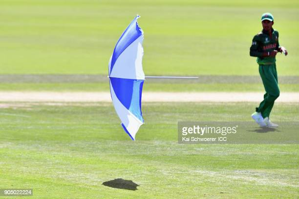 A parasol flies onto the field during the ICC U19 Cricket World Cup match between Bangladesh and Canada at Bert Sutcliffe Oval on January 15 2018 in...