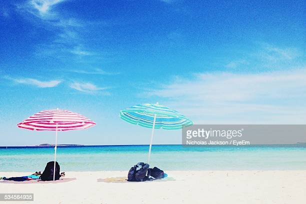 Parasols And Backpacks On Beach Against Blue Sky